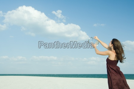 woman standing on beach holding up