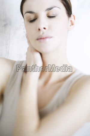 woman holding neck eyes closed