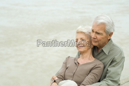 senior couple sitting together cheek to