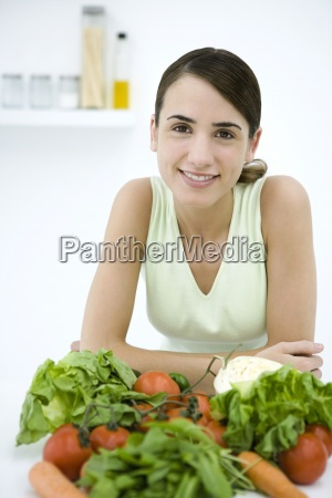 woman leaning behind assorted fresh vegetables