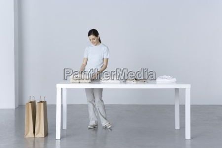 woman standing at table looking at
