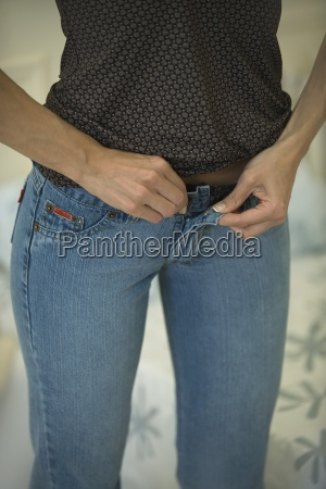 woman fastening tight jeans cropped view
