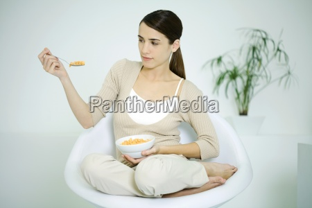 young woman sitting in chair holding