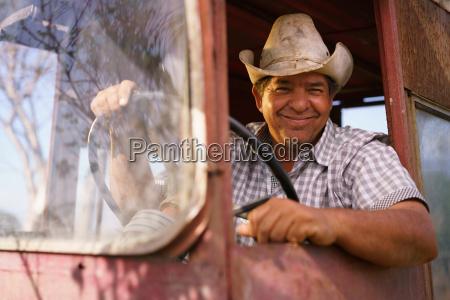 portrait happy man farmer driving tractor
