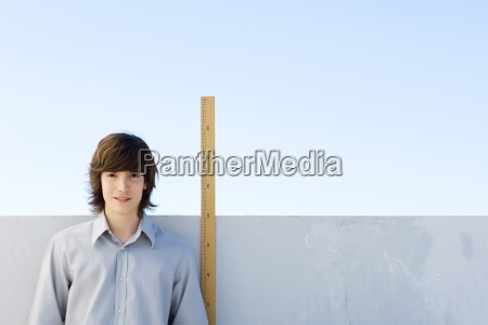 young man standing beside yardstick smiling
