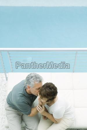 couple sitting on balcony man kissing