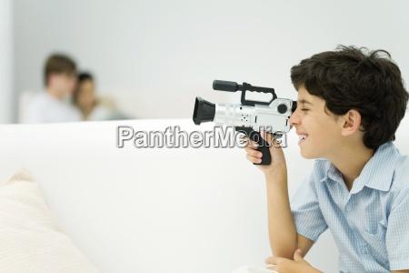 boy looking through video camera couple