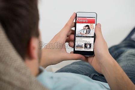 man reading online news on mobile