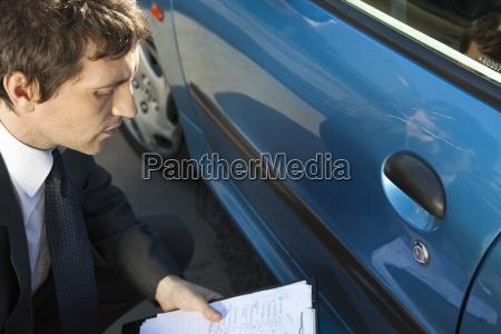 insurance adjuster examining damage to car