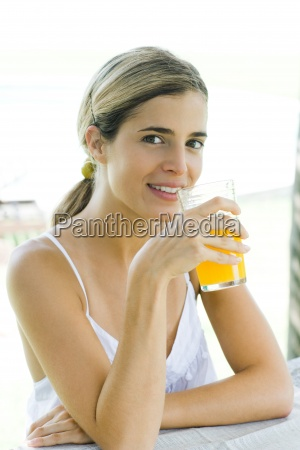 young woman holding glass of orange