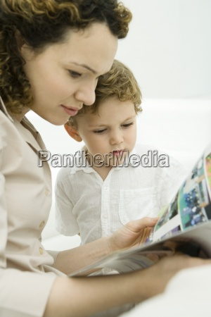 mother and toddler son reading comic