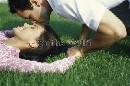 young couple relaxing on grass man