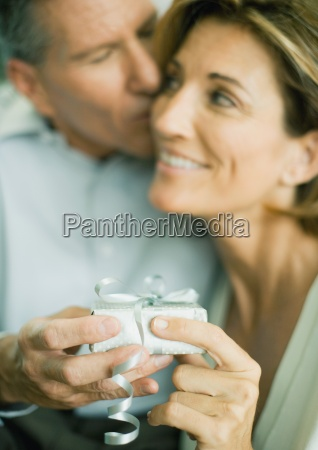 mature couple with present man kissing