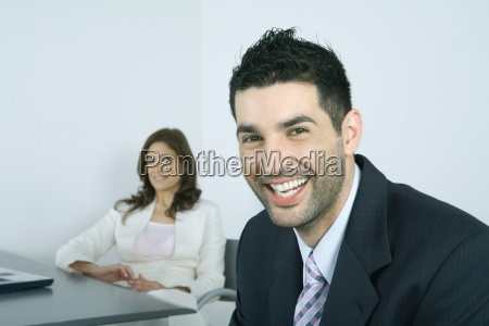 businessman laughing colleague in background
