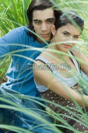 young couple sitting in grass looking