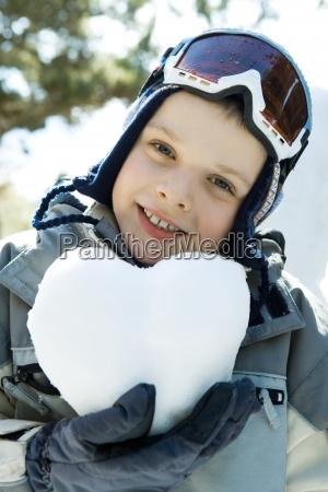 boy in ski gear holding heart