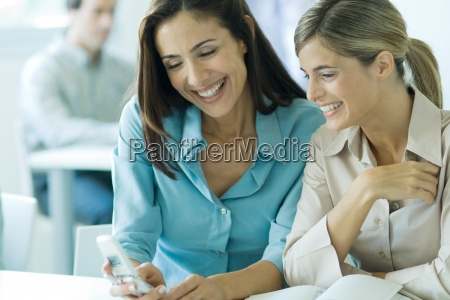 two businesswomen looking at cell phone