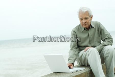 senior man sitting on low wall
