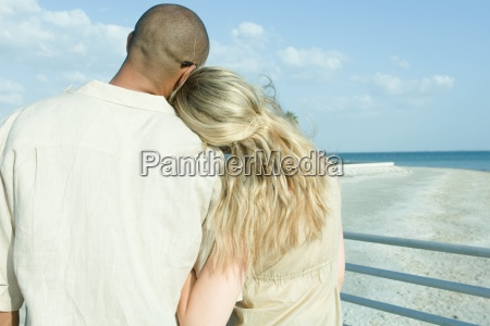 couple standing arm in arm looking