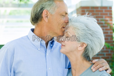 mature man kissing wifes forehead side