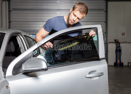 applying tinting foil onto a car