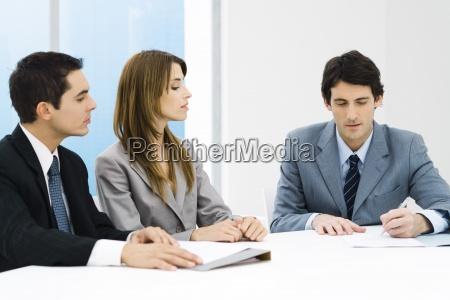 business associates in meeting man signing