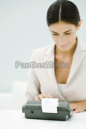 female accountant using adding machine looking