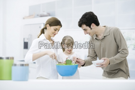 little girl helping parents cook in