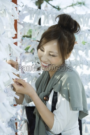 young female reading traditional japanese omikuji