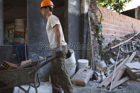 construction worker moving wheelbarrow through construction