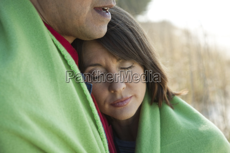 mature couple sharing blanket outdoors woman