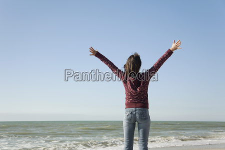 woman standing on beach with arms