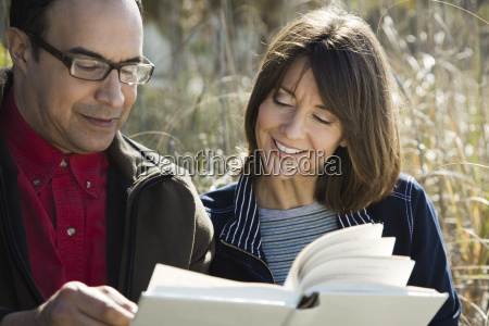 mature couple reading book together outdoors