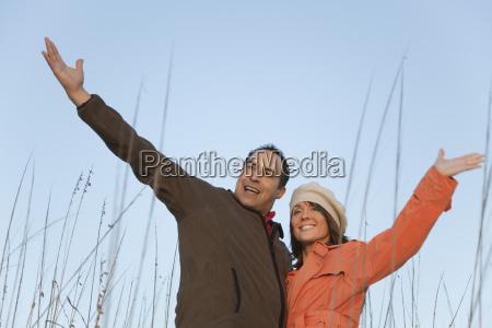 mature couple outdoors arms raised portrait