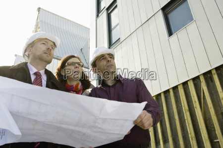 building contractor and architects discussing blueprint