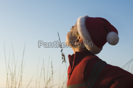 boy wearing santa hat outdoors contemplatively