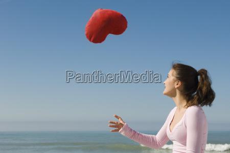 preteen girl at beach tossing stuffed