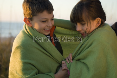 children wrapped together in blanket outdoors