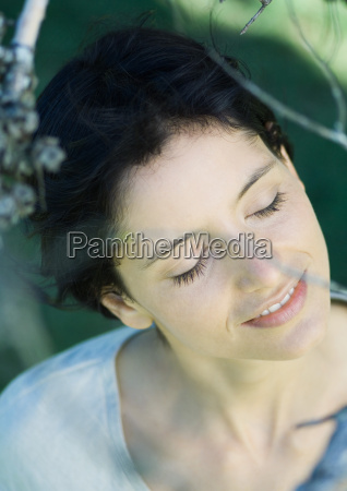 woman standing under tree head and