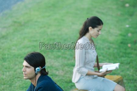 people sitting in park man listening