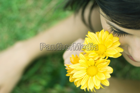 woman holding flowers up to face