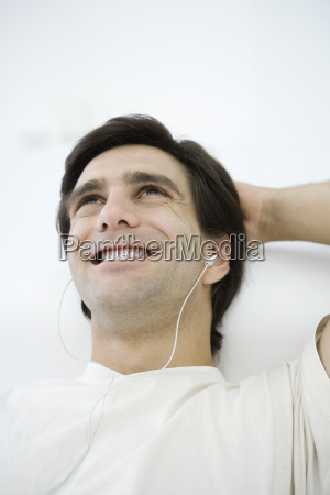 man listening to earphones smiling one