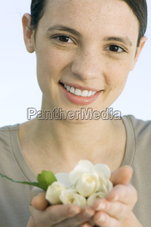 young woman holding handful of white