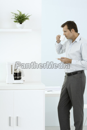 man standing by coffee maker taking