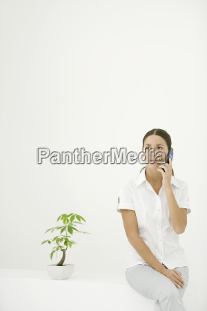 woman sitting beside potted plant using