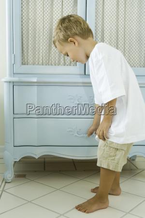 little boy peeking into drawer