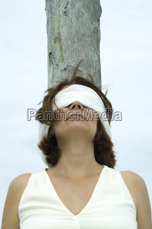 blindfolded woman leaning against tree trunk