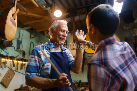 senior man lute maker teaching boy