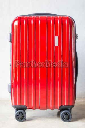 red travel suitcase for outgoing
