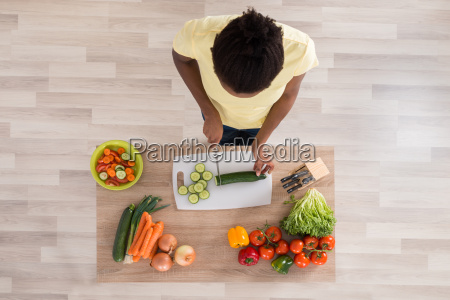 young african woman chopping vegetables in